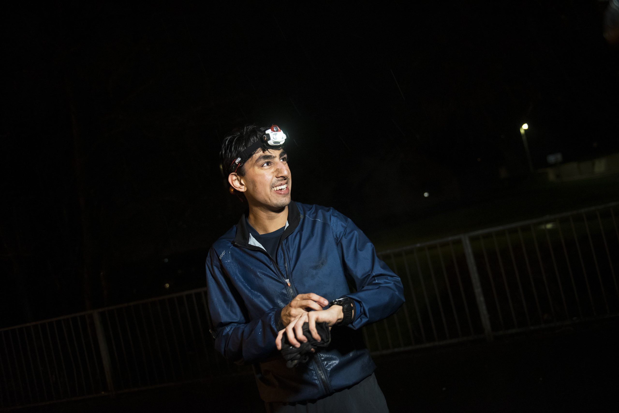 Runner with headtorch checking Garmin